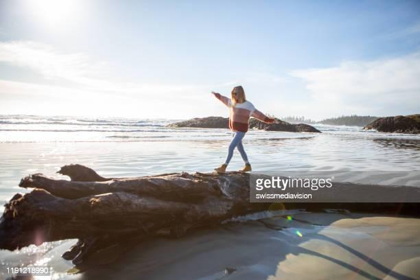 junge frau zu fuß auf baumstamm am strand balancieren körpergewicht - gleichgewicht stock-fotos und bilder