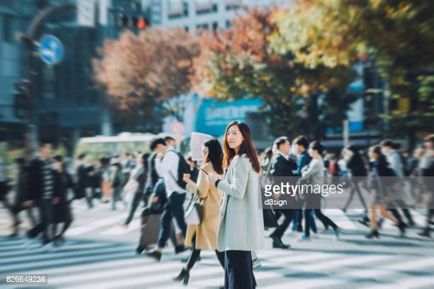 Young woman walking on zebra crossing and using smartphone in city