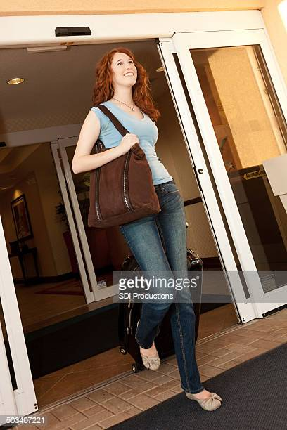 Young woman walking out of hotel carrying luggage