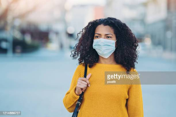 young woman walking outdoors with a face mask - pollution mask stock pictures, royalty-free photos & images