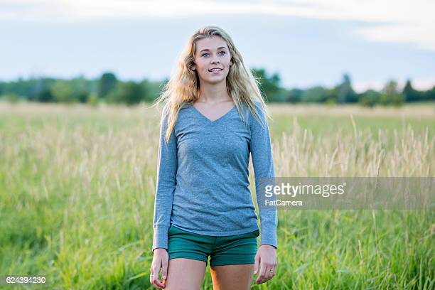 young woman walking outside - long sleeved stock photos and pictures