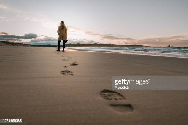 young woman walking over a beach and leaving her footprints on the sand - footprint stock pictures, royalty-free photos & images
