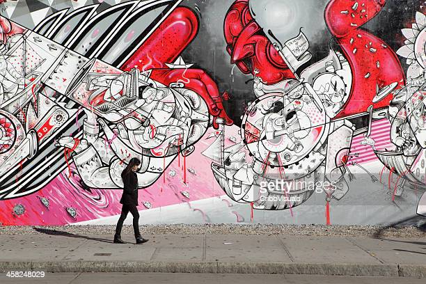 NYC young woman walking past How Nosm street art mural