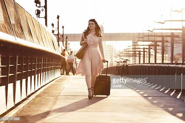 歩道を歩いて若い女性用のスーツケース