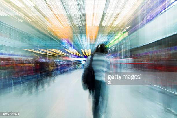 Young Woman Walking Through Airport Terminal, Blurred motion