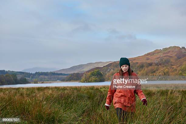 Young woman walking through Autumnal landscape