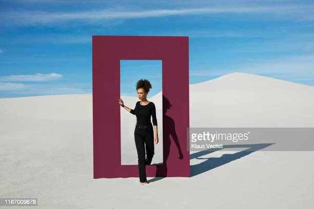 young woman walking through door frame at desert against sky - stepping stock pictures, royalty-free photos & images