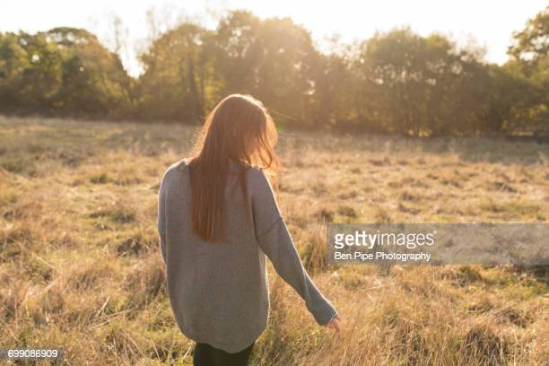Young woman walking through field in autumn, rear view