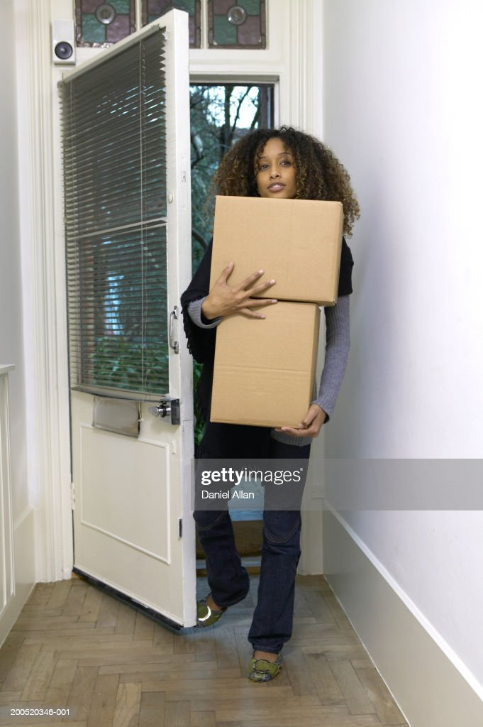 walking through front door. Young Woman Walking Through Front Door Of House, Carrying Boxes : Stock Photo
