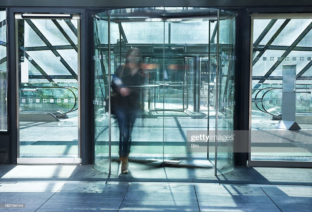 Young Woman Walking Through Glass Revolving Door Blurred Motion
