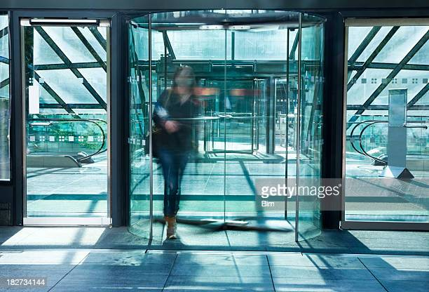 young woman walking through glass revolving door, blurred motion - revolve stock photos and pictures