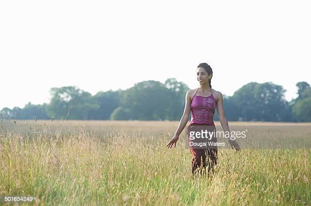 Young  woman walking through grasses