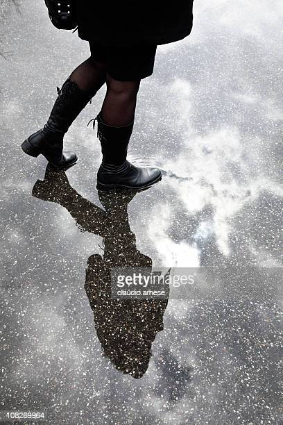 Jeune femme marchant par Flaque sur journée nuageuse