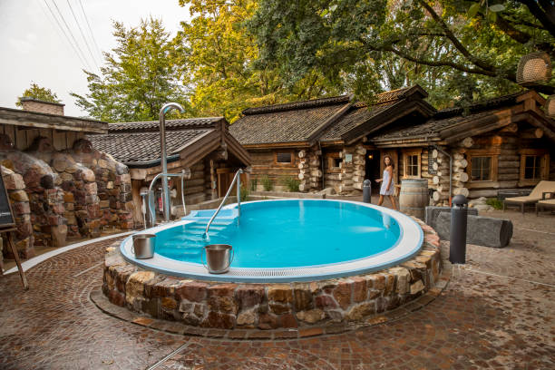 Young woman walking through spa garden next to swimming pool and sauna huts