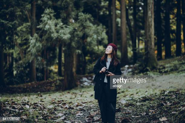 Young woman walking through the forest and exploring the nature