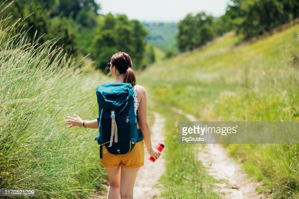 young woman walking through the mountain paths and enjoying - tourism stock pictures, royalty-free photos & images
