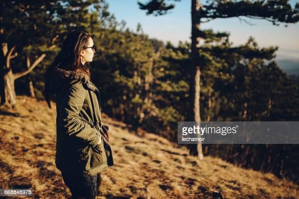 Junge Frau, die zu Fuß durch die Bergwälder