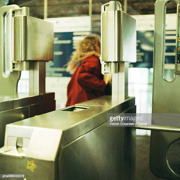 Young woman walking through turnstile, view from the rear.