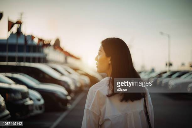 young woman walking to her car along outdoor car park in city at sunset - suchen stock-fotos und bilder