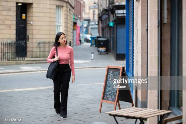 young woman walking to her hairdressers - ambient light stock pictures, royalty-free photos & images