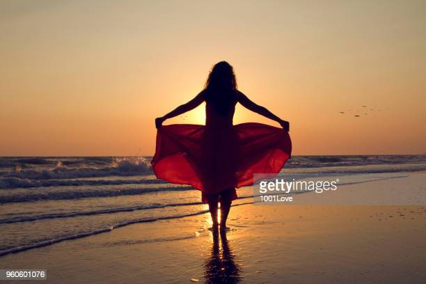 Young woman walking to the sun at beach. Freedom concept. Elegance at sunset.