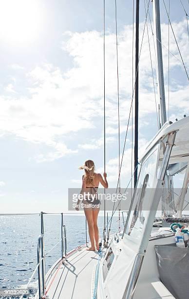 Young woman walking towards bow of sailboat