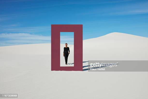 Young woman walking towards door frame on white sand dunes