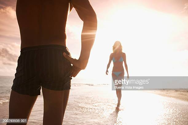 young woman walking towards man on beach at sunset - wading stock pictures, royalty-free photos & images