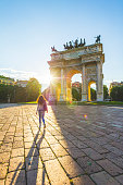 Young woman walking towards the Arch of Peace. Milan, Italy.