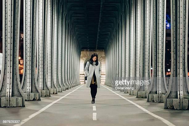 Young woman walking under highway bridge