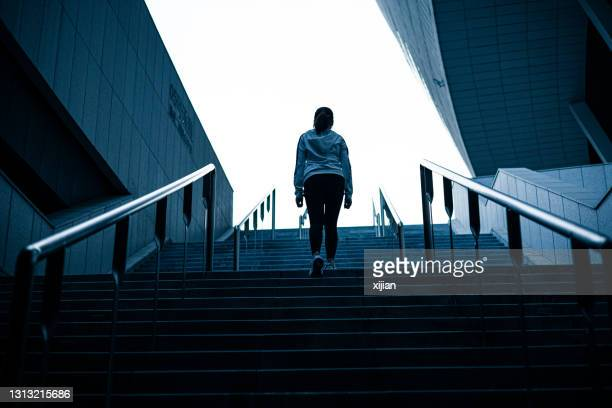 young woman walking up stairs - moving up stock pictures, royalty-free photos & images