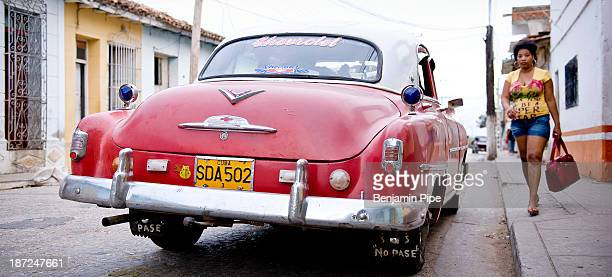 CONTENT] Young woman walking up to Vintage american Car parked on street Trinidad Cuba