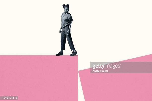 young woman walking while looking back at block - courage photos et images de collection