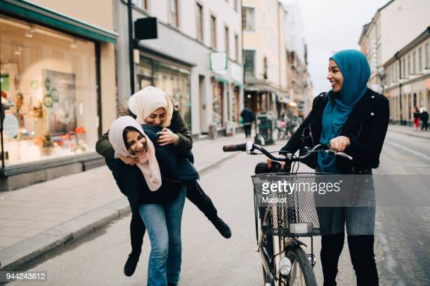 Young woman walking with bicycle looking at cheerful teenage girl giving piggyback to friend on street in city