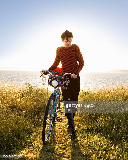 Young woman walking with bicycle, near water
