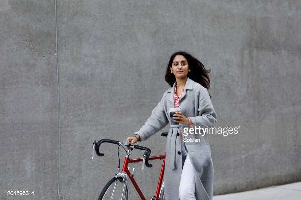 young woman walking with bicycle, with reusable coffee cup in hand - frauenpower stock-fotos und bilder