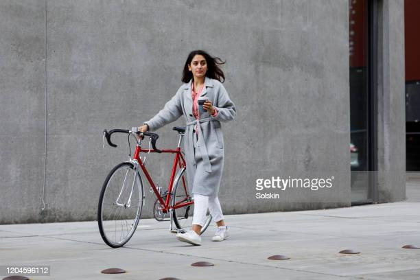 young woman walking with bicycle, with reusable coffee cup in hand - city life photos et images de collection