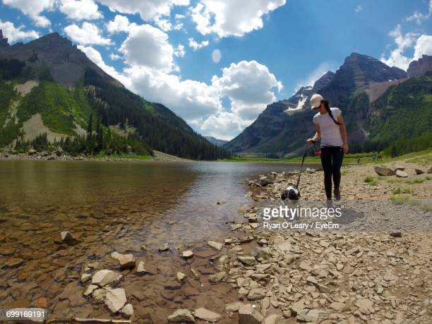 Young Woman Walking With Dog At Lakeshore Against Mountains