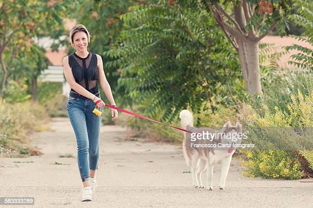 Young woman walking with her husky dog