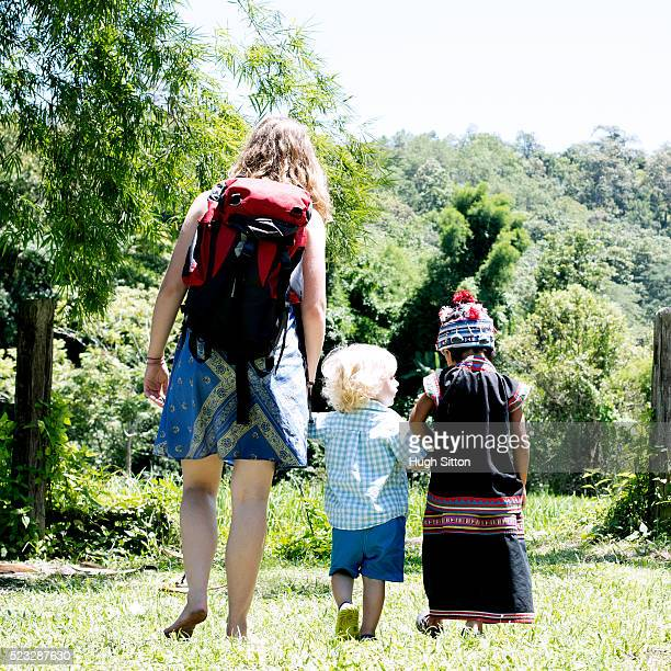 young woman walking with her son (12-23 months) and local child (4-5), chiang mai, thailand - hugh sitton stock pictures, royalty-free photos & images