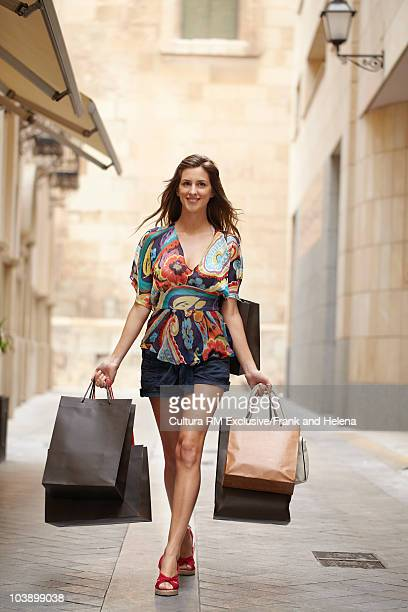 young woman walking with shopping bags - helena price stock-fotos und bilder