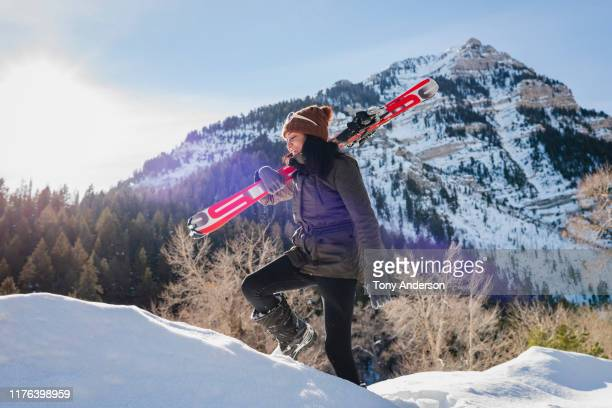 Young woman walking  with skis in winter mountains