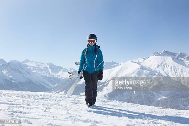 Young woman walking with snowboard