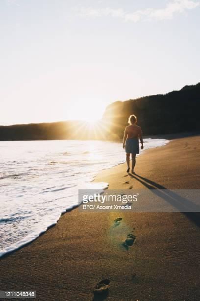 young woman walks along empty beach - azores fotografías e imágenes de stock
