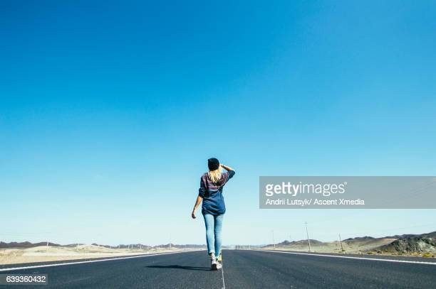 young woman walks along long rural highway - horizon over land stockfoto's en -beelden