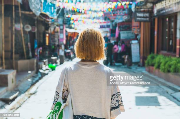 young woman walks along street market - mid length hair stock pictures, royalty-free photos & images