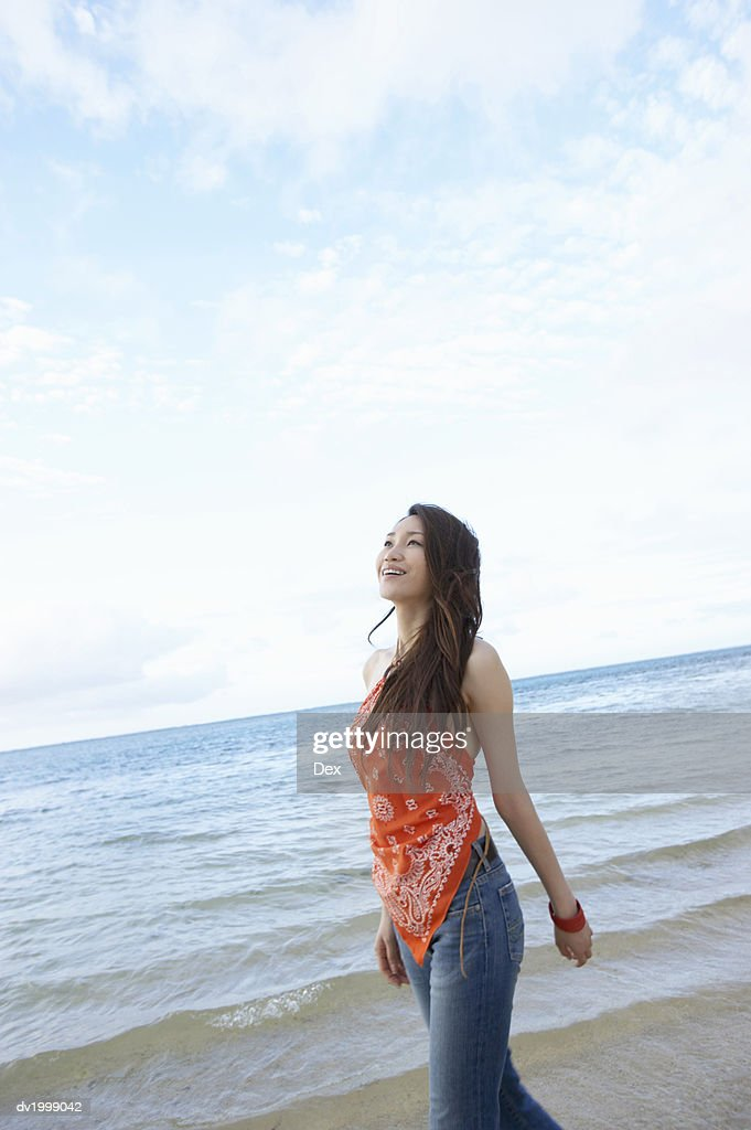 Young Woman Walks by the Sea, Looking up With Hope : Stock Photo