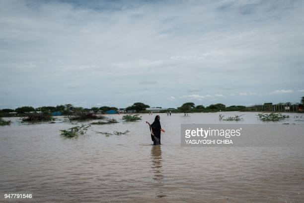 Young woman walks in floodwaters after a heavy rainy season downpour as they seek to fill sandbags at the Dadaab refugee complex, in the north-east...
