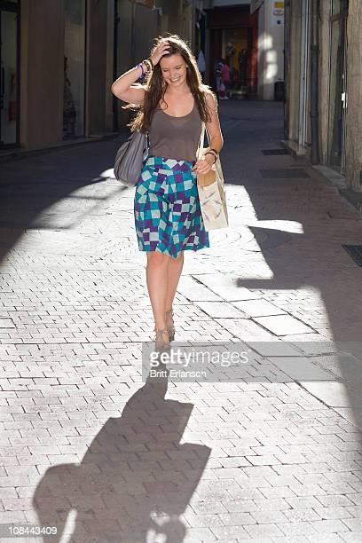 Junge Frau geht auf Straße mit Taschen