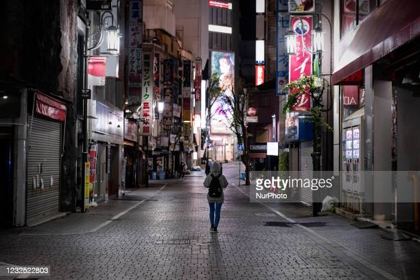 Young woman walks on the deserted street at downtown in Tokyo, Japan on April 25, 2021.